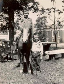 "Sammy Robertson astride ""Binki"" the Shetland Pony. Younger Brother Ronnie is alongside. Siloam Baptist Church and the Pam Am Station is in the background. You can see the Pan Am sign just to the left of Binki's head."