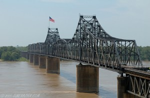 Old Vicksburg Bridge. Open span over the navigation channel is 825 feet. High water covers a small sandy beach on the west side of the river. The total shoreline to shoreline width at this point is no less than 3/4 of a mile. The current is very swift. This picture is a copyrighted work of Jim Frazier and is used under the principle of creative commons.